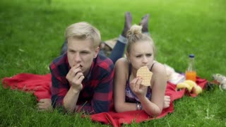 Couple lying on the blanket in the park and eating snacks