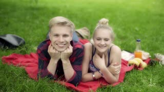 Couple lying on the blanket in the park and smiling to the camera