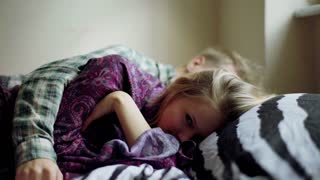 Couple lying together on the bed and girl looking tired