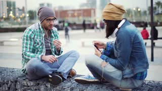 Couple of hipsters listening music while sitting in the city