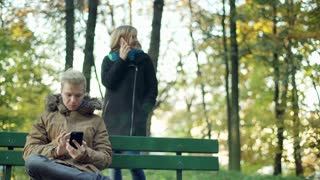 Couple relaxing in the autumnal park and using electronics