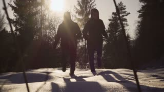 Couple running in the forest on snow, steady, slow motion shot at 240fps