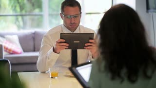 Couple sitting at the table and using tablet, steadycam shot