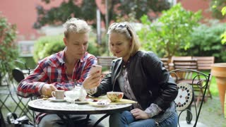 Couple sitting in the outdoor cafe and browsing internet on smartphone