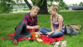 Couple sitting in the park and feeding each other with strawberries