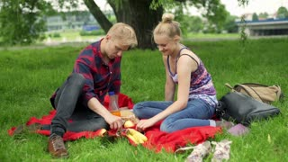 Couple sitting in the park and having a picnic
