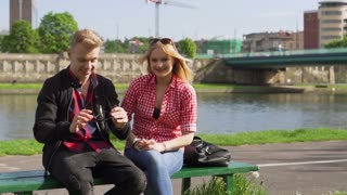 Couple sitting in the public place and smiling to the camera