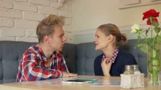 Couple sitting in the restaurant and talking with each other