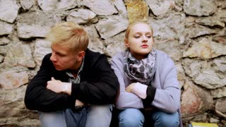 Couple sitting next to the brick wall after quarrel