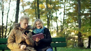 Couple sitting on the bench in the autumnal park and using electronics