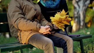 Couple sitting on the bench in the autumnal park