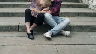 Couple sitting on the stairs and cuddling to the camera