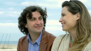Couple smiling to each other at the seaside, steadycam shot, slow motion shot at