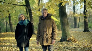 Couple standing in the autumnal park and smiling to the camera