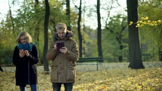 Couple standing in the autumnal park and using electronics