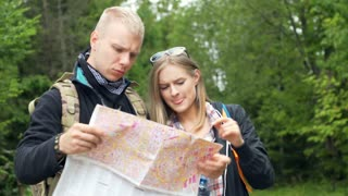 Couple standing in the forest and talking while looking on the map