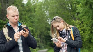 Couple standing in the forest and using modern technology