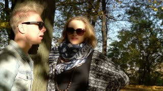 Couple standing in the park and chatting, steadycam shot, slow motion shot at 24