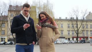 Couple standing on public square and using cellphones
