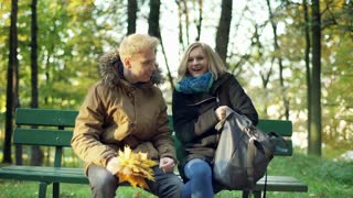 Couple talking and sitting on the bench in the autumnal park