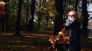 Couple throwing leaves in the park, slow motion shot