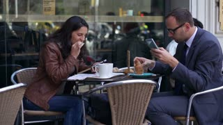 couple using cellphones and eating breakfast outside the cafe, slow motion