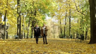 Couple walking in the park and browsing internet on smartphone
