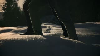 Couple walking on deep snow at sunset, steady, slow motion shot at 240fps