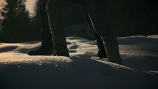 Couple walking on deep snow at sunset, steadycam shot, slow motion shot