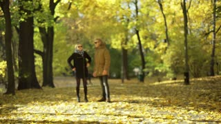 Couple walking on the pathway in the autumnal park and chatting