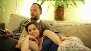 Couple watching comedy on tv on sofa at night.