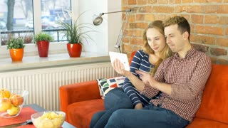 Couple watching something funny on the tablet, steadycam shot