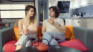 Couple wearing pajamas and looking upset while talking on the sofa