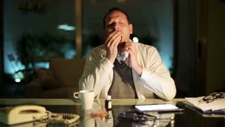 Doctor falling asleep at desk in office at night.