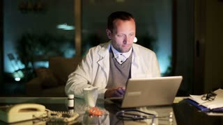 Doctor finish work on laptop at night in office and drinking coffee.