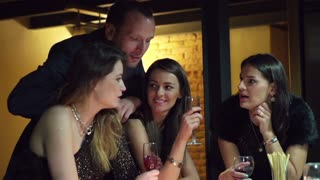 drunk man bothering women in conversation at party, slow motion shot at 120fps
