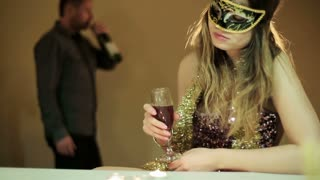 drunk woman in a mask with a glass of wine  and a drunk man in the background
