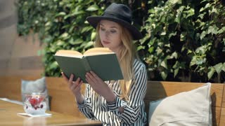 Elegant woman in black hat sitting in the cafe and reading book