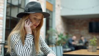 Elegant woman in black hat sitting in the outdoor cafe and chatting on cellphone
