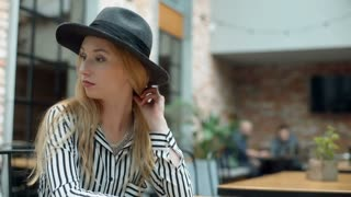 Elegant woman takes off her black, stylish hat while sitting in the cafe
