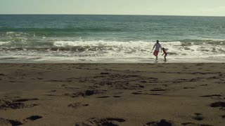 Father playing with his son and running on the sandy beach, steadycam shot