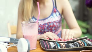 Female hands taking smartphone from stylish, colorful bag