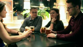 Friends chatting in the pub and drinking beer, steadycam shot