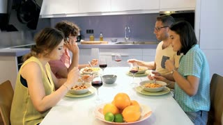 Friends eating dinner together and chatting on cellphone