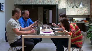 Friends eating supper and looking on cellphone