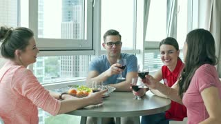 Friends sitting together in the apartment and drinking wine