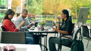 Friends using modern technology and relaxing in the street cafe, steadycam shot