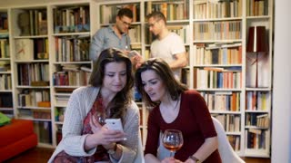 Friends using smartphone and chatting at the party