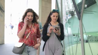 Friends walking in the city and using modern technology