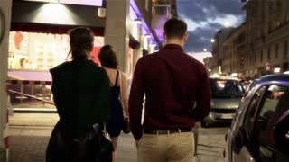 Friends walking in the city at night, steadycam shot
